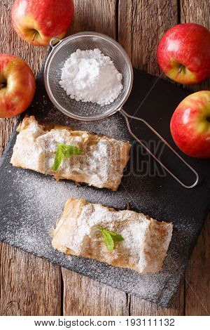 Austrian Food: Apple Strudel With Powdered Sugar And Mint Closeup On The Table. Vertical Top View