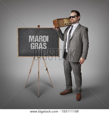Mardi Gras text on blackboard with businessman holding radio