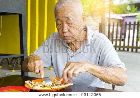 asian senior man having roti canai outdoor
