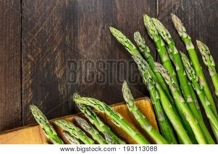 An overhead photo of fresh asparagus stalks on rustic textures with a place for text