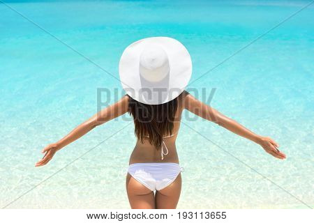 Beach vacation bikini woman with open arms in freedom. Carefree girl from behind in white swimwear and sunhat. Weight loss butt cellulite concept.