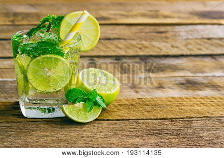 Lemonade in glass put on rustic wood table. Lemon or lime and mint leaf in sparkling water. Lemon or lime soda make fresh and cool for summer. Lemonade or lime juice on plank with copy space for background.