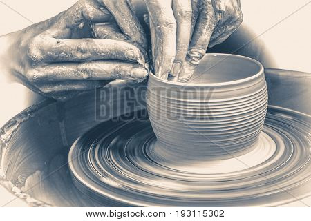 Old vintage photo.Master class on modeling of clay on a potter's wheel In the pottery workshop. Old vintage style.