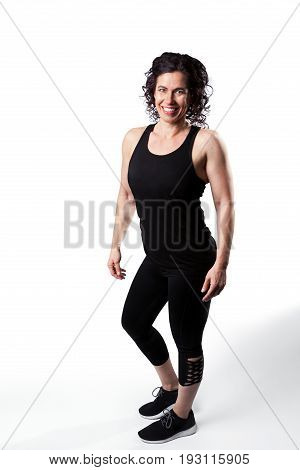 A full length pose of a muscular female in workout attire. She is on a white background.