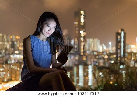 Woman use of mobile phone with the background of city