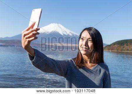 Woman taking selfie with mobile phone in Fujisan