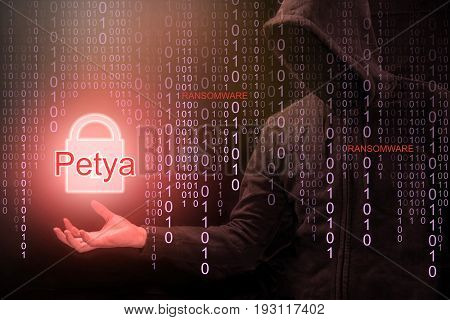 Male hacker show Petya or Petrwrap ransomware and red padlock symbol on hand with digital binary code in foreground. cyber attack and internet security concepts