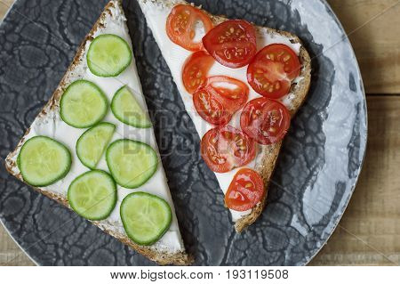 Breakfast toasts with soft cream cheese red cherry tomatoes and cucumber slices. Healthy sandwiches