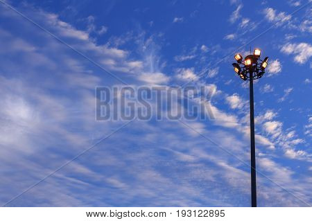 Large tall high outdoor stadium halogen spotlight with lamp light turned on and sky clouds in twilight.