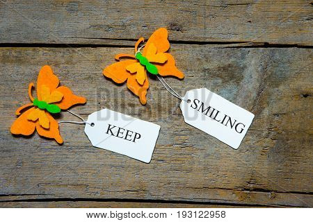 Felty Butterflies And White Signs On Wooden Table, Keep Smililng