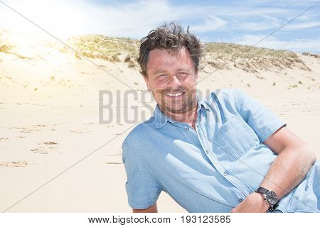 a Handsome 40-year-old man lying on beach