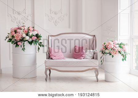Interior of a snow-white living room with a vintage sofa and flowers.