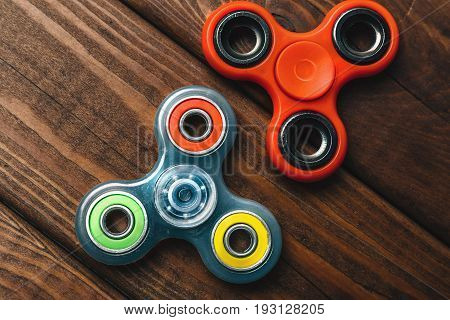 Two Fidget Spinners popular trend stress relieving toy on wooden background, top view