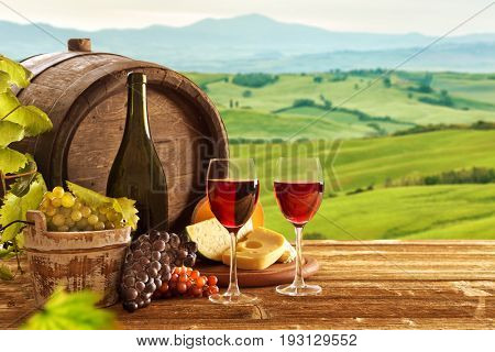 red wine bottle and wine glasses with wodden barrel. Tuscany landscape.