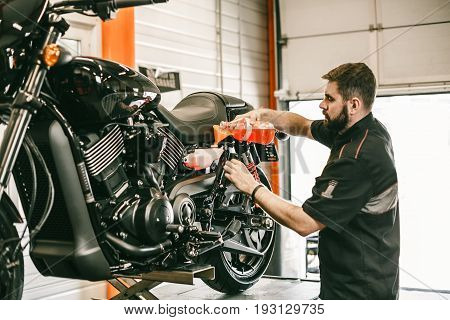Professional mechanic pouring antifreeze into a motorcycle. Confident young man repairing motorcycle in repair shop.