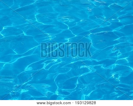 pattern of ripples on blue water surface in swimming pool, abstract natural background