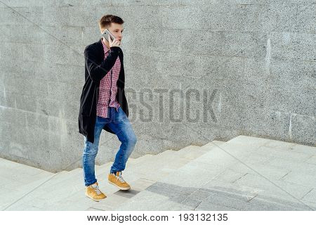 Stylish young man in plaid shirt and jeans walking up stairs and talking on cell phone, full body. Student with smartphone walking up stairs, free space