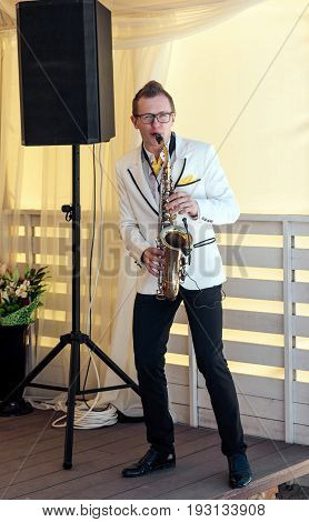 Saxophonist in white jacket playing the saxophone. Saxophonist jazz man with saxophone on wedding party full body