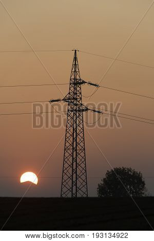Electricity Pylon In Silhouette At Sunset