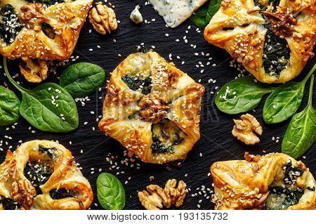 Spinach puffs with addition of Gorgonzola cheese, walnuts and sesame seeds on  black background, top view