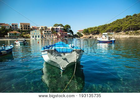 Boat in the marina in Assos village Kefalonia island Greece. Greek Islands cityscape.