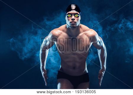 Attractive and muscular swimmer. Studio shot of young shirtless sportsman on black smoke background. Man with glasses