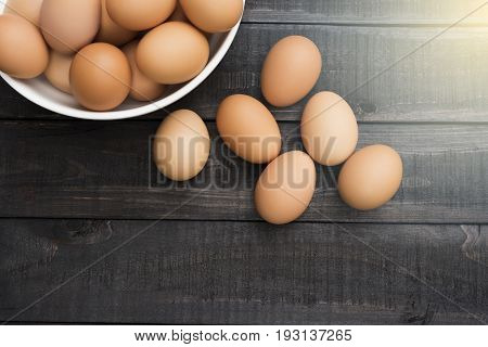 Fresh hen egg in white bowl and 6 hen egg out side on Black color wood table