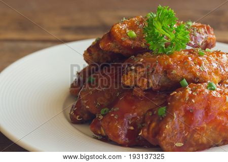 Barbecue chicken wings on white plate in close up view. Homemade barbecue chicken wing delicious moist and spicy. Deep fried chicken with barbecue sauce decorated with spice and parsley ready to served.