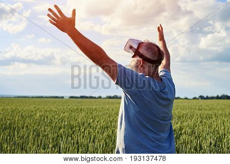 Rear view, male rising hands up to the sky, enjoying virtual reality in 3D glasses outdoors on field, mid shot