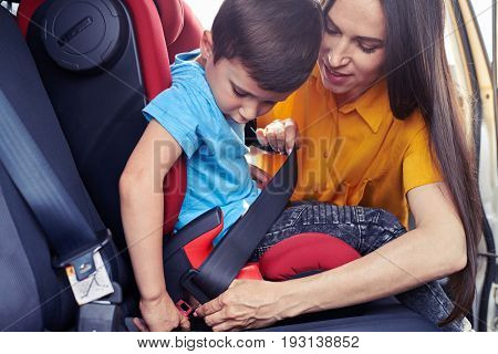 Mid shot of beautiful woman helping son sitting in baby seat to fasten seat belt