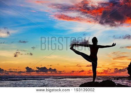 Sunset meditation. Active woman stand in yoga pose on beach rock to keep fit and health. Healthy lifestyle fitness training sport activity on summer family holiday.