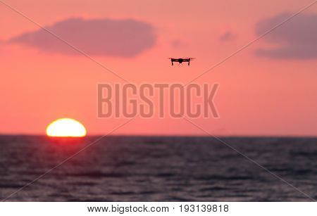 Drone flies over a colourful sunrise sky. New technology concept.