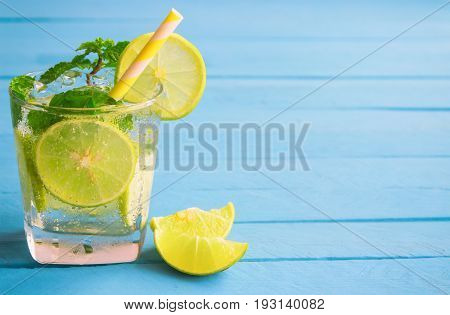 Lemonade in glass put on light blue wood table with blank space for background. Lemon or lime and mint leaf in sparkling water or soda. Lemon or lime mojito make fresh and cool for summer. Lemonade or lime juice with copy space.