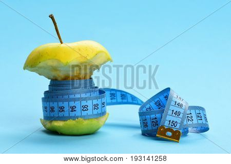 Healthy nutrition composition. Green bitten apple tied with blue sewing centimeter isolated on light blue copy space