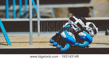 Toned baner Roller inline skates in skate park on gray urban background. Street culture