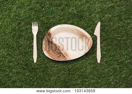 Top View Of Wooden Plate With Fork And Knife On Grass