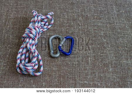 Striped nylon rope and two carabine on a background of sackcloth. Close up.