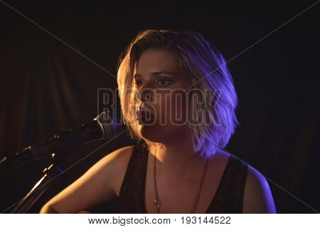 Close up of confident female singer performing in music concert