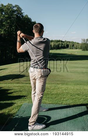 Back View Of Man Holding Golf Club While Playing Golf Outdoors