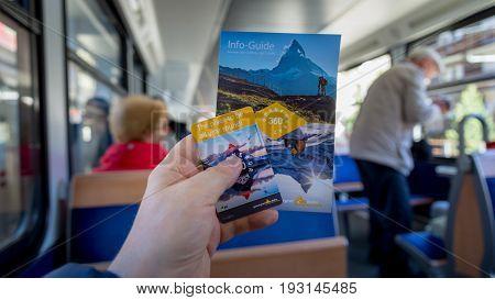 ZERMATT, SWITZERLAND - May 16. 2017: Gornergrat booklet and ticket in hand in the Red train climbing up to Gornergrat station on Zermatt, Switzerland.