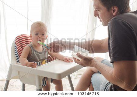 Careful father feeding little boy sitting in child chair.