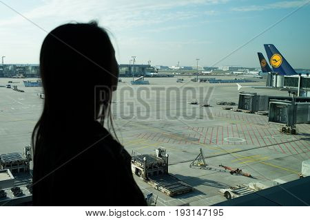 Frankfurt am Main Germany - October 11 2015: Woman in airport. Silhouette of girl looking at planes on airdrome ground on sunny day. Travelling by air. Aviation and transport. Vacation and adventure