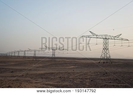 Electricity Pylons In Sand Desert