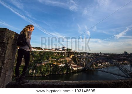 Young woman standing enjoying view of Douro river and Dom Luis I bridge, Porto, Portugal.