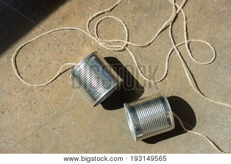 Top View Of Aluminium Tin Cans Connected With Rope On The Ground, Tin Cans Telephone