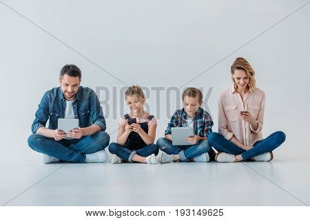 happy family using digital devices while sitting on the floor