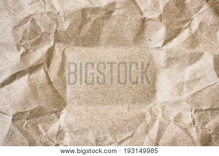 crumpled sheet of packing beige paper with space for text in middle secondary raw material