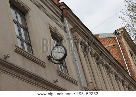 The wall clock on the outer bracket is attached to the wall and is located at the Street have a black color of the rim and white color of the dial are made antique