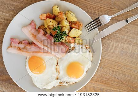 рlate with bacon potatoes and eggs on the table