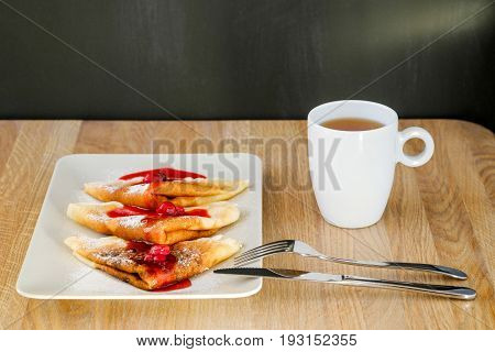 branded pancakes with syrup and hot tea